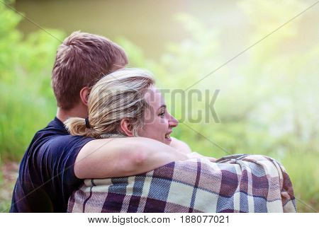 A married couple beautiful girl and boyfriend hugging in plaid plaid in the forest in the sunset light.