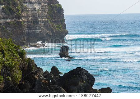 Rock in the sea against the background of cliffs. Bali Indonesia