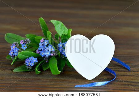 Fathers Day card with heart and flowers on wooden background