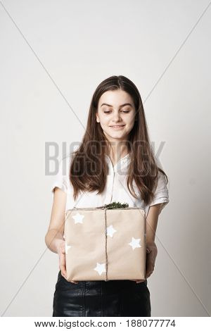 The girl is standing with a gift box. Isolated on white background. Beautiful young girl.