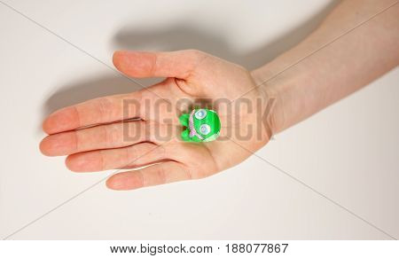 female hand showing small green monster made of plasticine