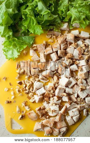 Chopped Ruddy Chicken Breasts With Leaf Salad And Crushed Walnut On Yellow Cutting Board.