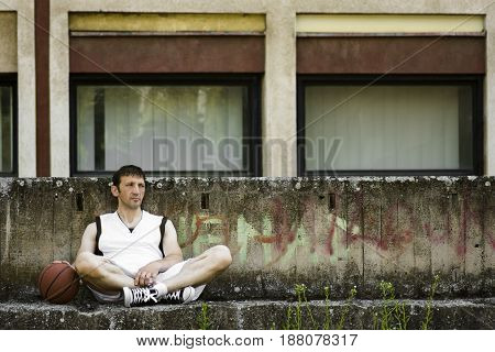 The tired basketball player is resting and sitting after match outdoors in the city.