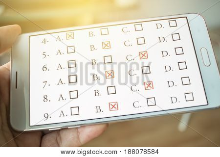 student testing quiz in exercise online exams answer on smart phone with multiple-choice check for evaluation questions by digital internet in hands