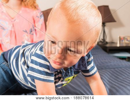 One Baby Boy Crawling on Bed With Mother in the Background