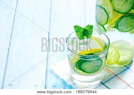 Detox water with lemon and cucumber. Bottle and drinking glass with slices of fresh fruit and vegetable, mint and rosemary. Blue plank background with cotton checkered napkins