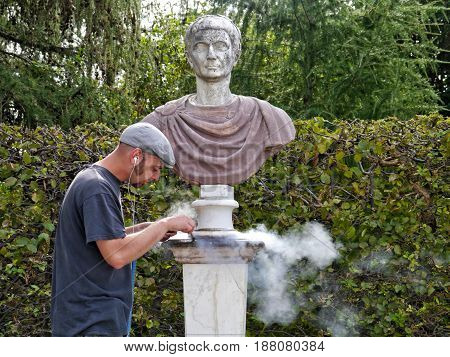 POTSDAM - GERMAY - SEPTEMBER, 2011: Park ensemble of Sanssouci. Working grinder restores one of the park statues in summer.