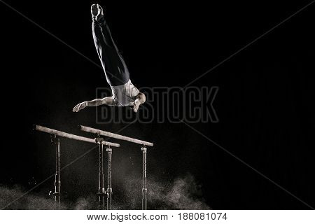 Male athlete performing difficult exercise on gymnastic parallel bars with talcum powder. Isolated on black