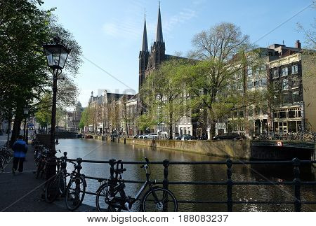 AMSTERDAM NETHERLANDS - MAY 13 2017: View from the bridge to the Church of St. Francis Javier on the Canal Zingel in Amsterdam