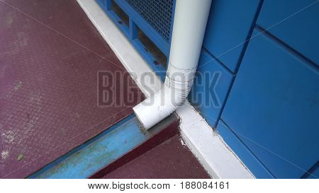 white downpipe on the background of blue wall.