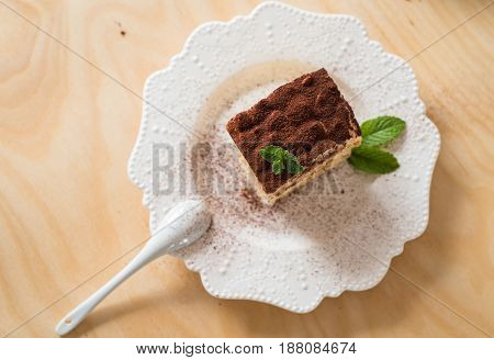 Tiramisu coffee cake served on a white plate wood background