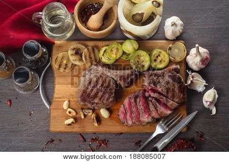 Grill meat rib eye steak composition on a wooden background