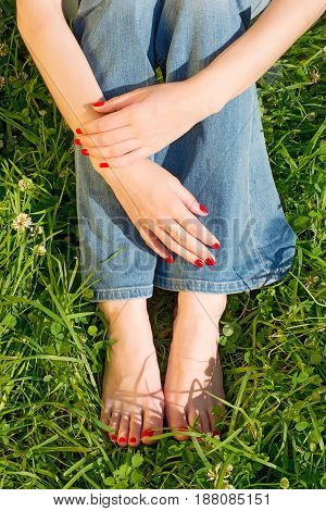 Woman in casual sitting on green grass. Hands and legs close up. Bright red manicure and pedicure on natural background