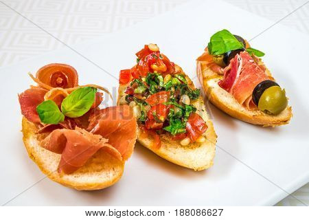 Delicious, Mouth-watering Different Canapes With Meat, Vegetables, Herbs And Olives, On A White Plat