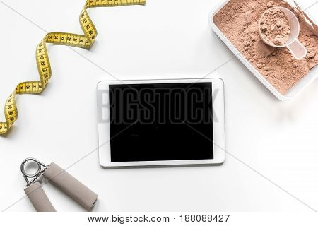 sport diet nutrition and fitness equipment , tablet, bars and measure tape on white background top view mock up