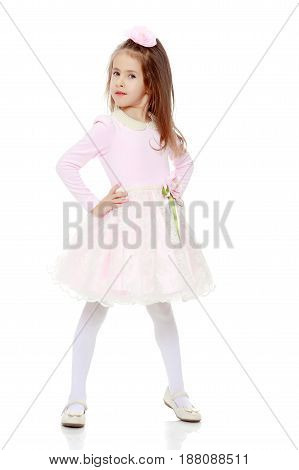 Dressy little girl long blonde hair, beautiful pink dress and a rose in her hair.She keeps hands on hips.Isolated on white background.