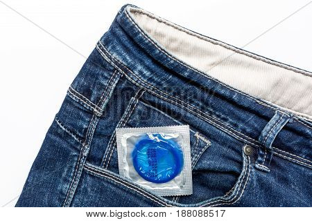 safe sex with condom contraception in jeans pocket on white desk background top view