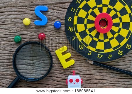 SEO (search engine optimization) concept with pencil dartboard magnifying glass on wood table.