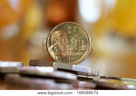 Australian two dollar coin on a bed of coins depicting an aboriginal man from the first nation.