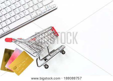 office desk with mini trolley and cards for online buying on white background top view mock-up