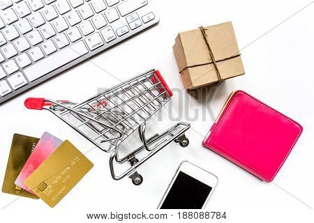 making purchase with credit cards and mini trolley on office desk background top view mockup