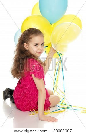 A beautiful little girl of primary school age, with long flowing hair, in a bright red dress.She sits on the floor and holds balloons in her hand.Isolated on white background.