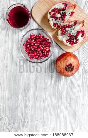 Red sliced pomegranate and juice in glass on light wooden background top view mock up