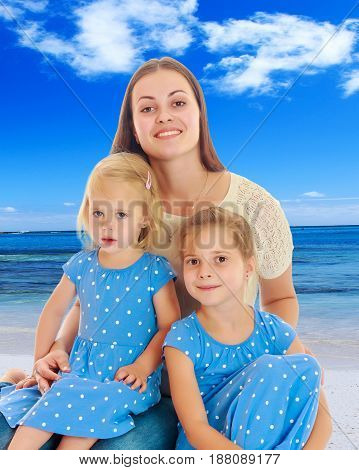 Beautiful young mother with her two daughters. Girls in the same dress with polka dots. Look directly at the camera.The concept of family happiness and mutual understanding between parents and children.