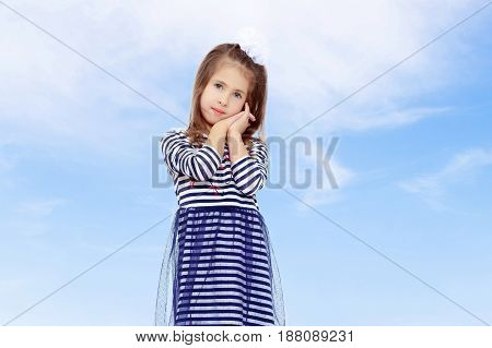 Beautiful little girl long hair and white bow on her head , in a summer dress in stripes.She holds the palm of your hand near the cheeks.On the background of summer blue sky and fluffy clouds.