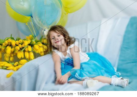 Beautiful little girl in a blue skirt tutu, sitting on the couch with a bouquet of yellow tulips.