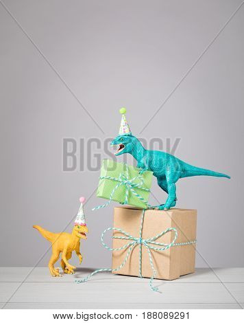 Two dinosaurs with birthday hats and gifts on a light grey background.