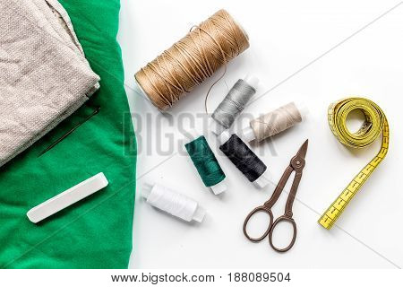 tailor workspace with sewing and handmade tools on white desk background top view