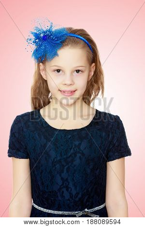 Cute Caucasian little girl In a dark blue dress and big blue bow on her head.Pale pink gradient background.