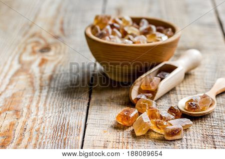 brown sugar cubes for cooking sweets on kitchen wooden table background