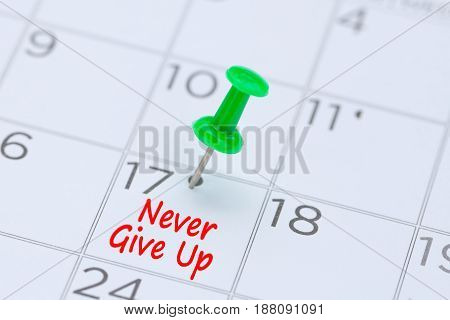 Never give up written on a calendar with a green push pin to remind you and important appointment.