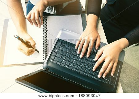 Top view of businesswoman meeting and typing keyboard with other mobile electronics on workspace desktop Female hands working on laptop computer Everyday office life concept