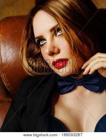 Young attractive girl in a jacket and bow tie. Femme fatale. Evening makeup smokey eye. She lies on a leather couch and looks coquettishly upwards.