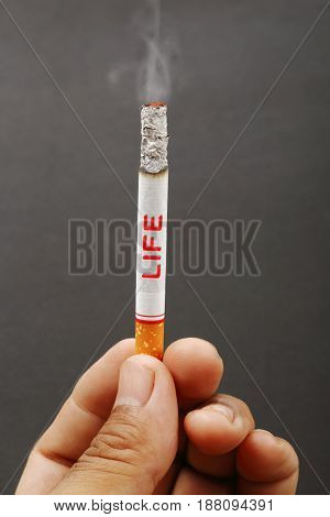 Smokers hand with life wording and cigarette burning on dark background.