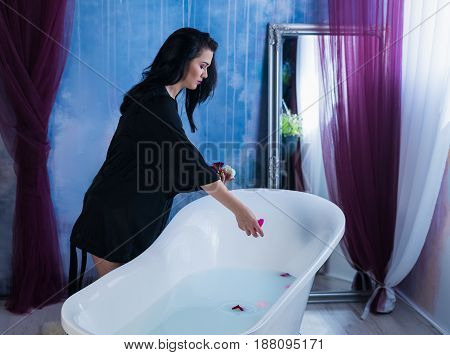 Woman in bath. Sexy brunette woman putting flowers to bathtube. Spa concept