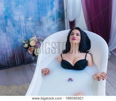 Woman in bath. Sexy brunette woman relaxing in hot milk bathtube with flowers. she is wearing black sexual lingerie