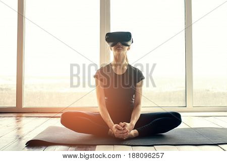 A young beautiful woman in virtual reality glasses makes aerobics remotely. Future technology concept. Classes in single sports remotely.