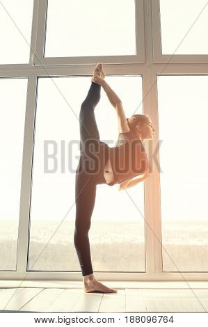 Young beautiful woman practicing yoga and gymnastic. Classes in single sports.