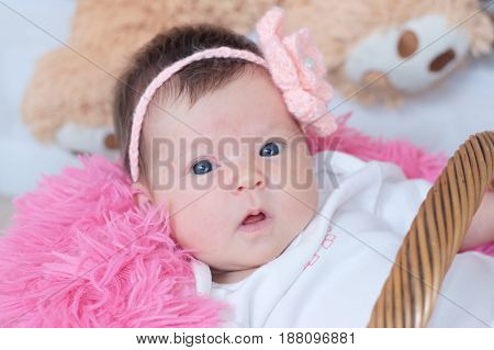 newborn baby girl portrait in pink blanket lying in basket cute face card composition new life