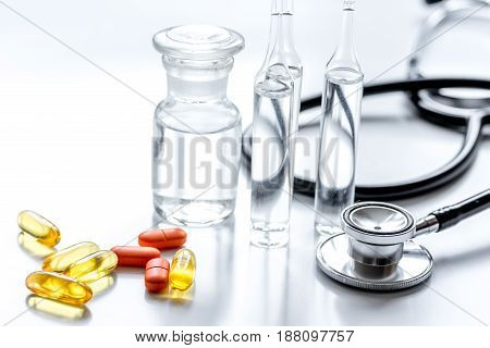 doctor's office table with pills, medicine glass bottles and stethoscope on white background