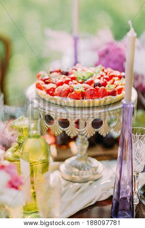 The wedding fruit sponge cake is decorated with the strawberries and cherries. It is placed on the board cake surrounded by romantic candles and wine