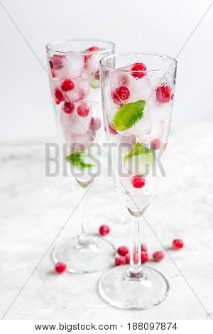 frozen red berries in ice cubes with mint in glasses on gray stone table background