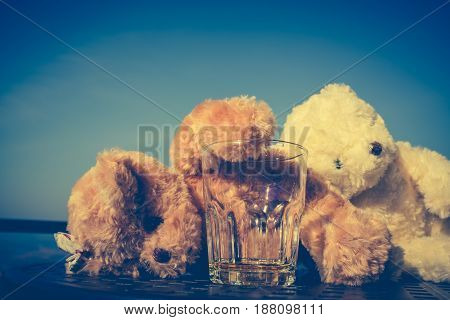 Teddy bears couple very drunk alcoholic and sleeping with empty glass on table. Alcohol is not good for health and don't drink concept. Vintage effect tone.