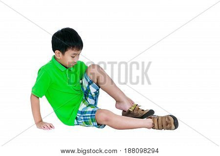 Side view of cute asian child put leather shoes on. Boy sitting on floor. Isolated on white background and free form copy space. Studio shot. Positive human emotion.