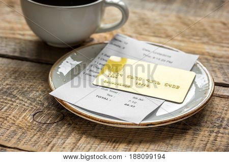 paying check for lunch in cafe with credit card on wooden table background