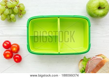 homemade lunch with apple, tomato and sandwich in green lunchbox on wooden table background top view